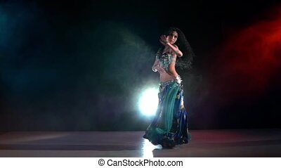 Slim, beautiful woman belly dancer sensetive dancing on blue, red, in smoke, slow motion