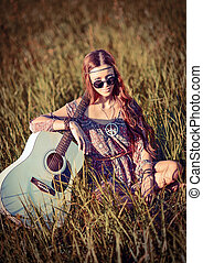 Lovely young hippie girl with guitar sitting on grass -...