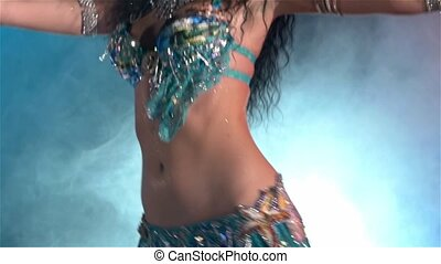 Middle section of a womans body dancing belly dance, in...