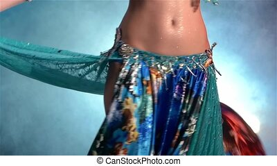 Middle section of a woman's body dancing belly dance, in...