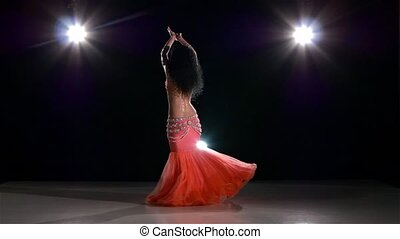 Pretty belly dance woman bellydancer dancing on black, back...