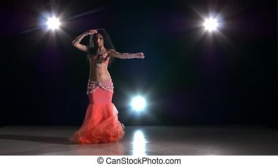 Belly dance of attractive girl, on black, back light, slow...