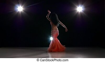 Belly dance of young girl, on black, back light, slow motion...