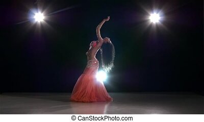 Belly dance of beautiful girl in pink, on black, back light,...