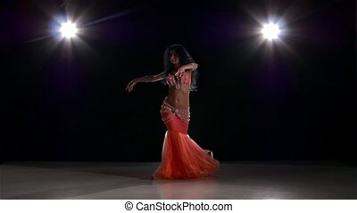 Belly dance of beautiful girl in pink dress, on black, back...