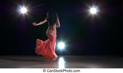 Belly dance of beautiful girl in shiny pink dress, on black, back light, slow motion