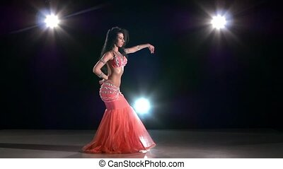 Young girl in pink oriental costume dancing belly dance, on...