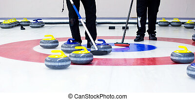 Curling - Two players with brooms on the ice, determining...