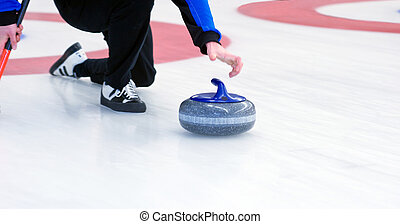 Curling player delivering a stone on a curling rink, sliding...