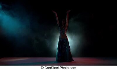 Beautiful belly dance movement, slow motion, in smoke, black...