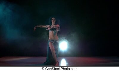 Beautiful belly dance movement of young girl, slow motion, in smoke, black
