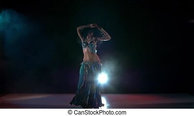 Beautiful belly dance movements of young and attractive girl, slow motion, in smoke, black