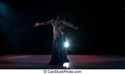 Professional belly dance movements of young and attractive girl, slow motion, in smoke, black