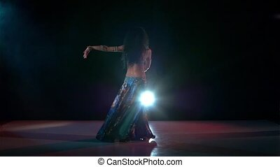 Talanted belly dance movements of young and attractive girl, slow motion, in smoke, black