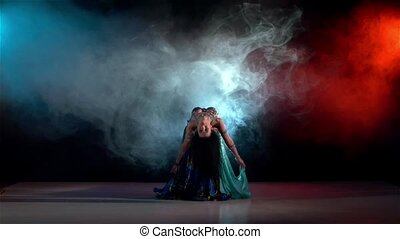 Talanted belly dance movements of young and attractive girl, slow motion, in smoke, black, red, blue