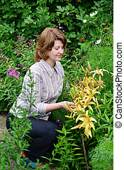 pretty woman looks after behind plants in the garden - Young...