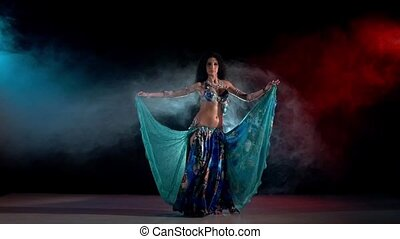 Sensetive belly dance movements of young and attractive girl in great dress, slow motion, in smoke, black, red, blue