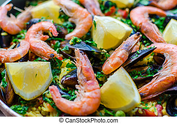 Close up classic seafood paella with mussels, shrimps and...