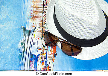 Summer background with glasses and hat on the blue fabric...