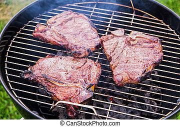 Fried Steaks on a Grill - Three t-bone steaks frying on a...