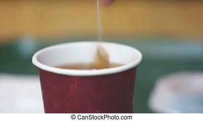 Dipping a tea bag in a cup. - Dipping a tea bag in a cup...