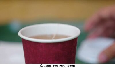 Dip teabag in take-away cup full of hot water