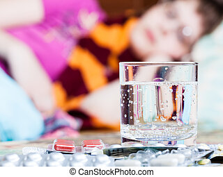 glass and pills on table close up and sick woman