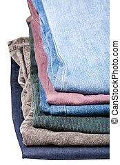 stack of various jeans and corduroys close up isolated on...