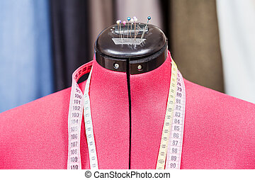 mannequin with measure tapes and clothes - red tailor dummy...