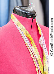 mannequin with measure tapes and ready dresses - red tailor...