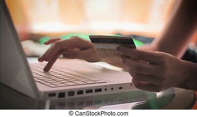 Woman entering information from a credit card using laptop
