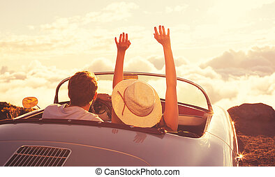 Young Couple Wathcing the Sunset in Vintage Sports Car -...