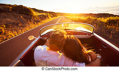 Romantic Couple Driving on Beautiful Road at Sunset -...