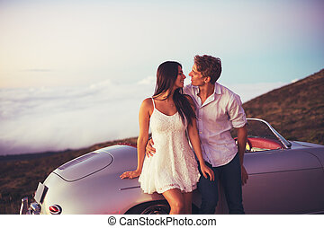 Couple Watching the Sunset with Classic Vintage Car -...