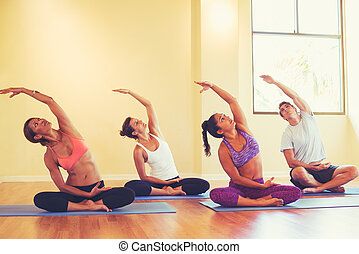 Young People Stretching in Yoga Class - Group of People...