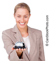Attractive businesswoman holding a service bell against a...