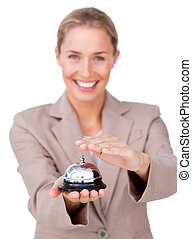 Smiling businesswoman holding a service bell against a white...