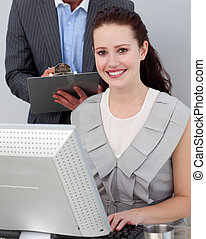Smiling young businesswoman working at a computer in the...