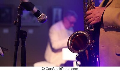 the man in the white suit playing the saxophone at the party