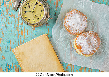 Sweet sugary donuts, book and vintage clock on rustic table...