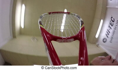 Playing squash. Racket and ball on a court.
