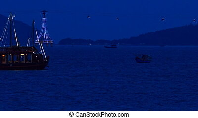 view of drifting vessel along bay at deep night  against city