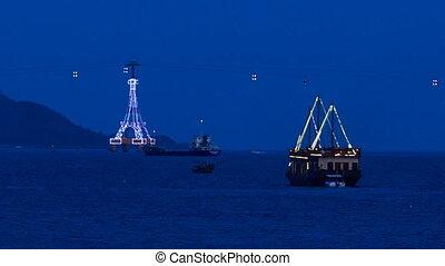 drifting ship along bay at night against ropeway and...