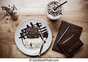 Brownie with ice coffee on wooden table and notebook.