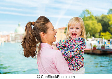 Laughing mother in profile holding happy daughter in Venice...