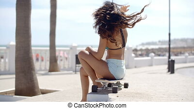 Sexy young woman sitting on her skateboard - Sexy young...