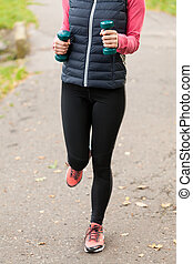 Woman running with dumbbells