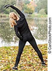 Woman warming up before training in park