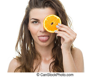 Girl sticking out tongue and holding orange slice