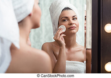 Woman removing makeup - Young beauty woman removing makeup...